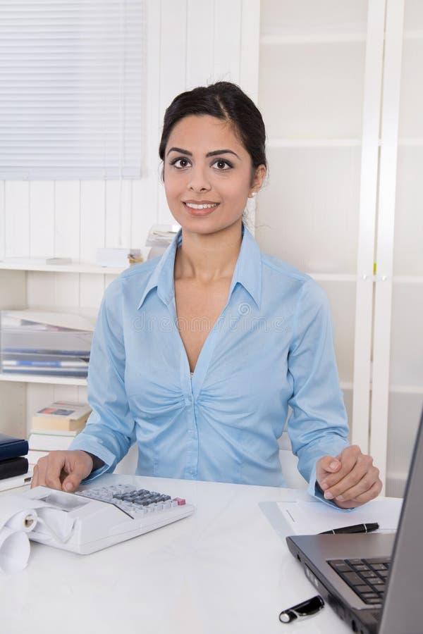 Ungt indiskt kvinnasammanträde på skrivbordet i hennes kontor. royaltyfri bild