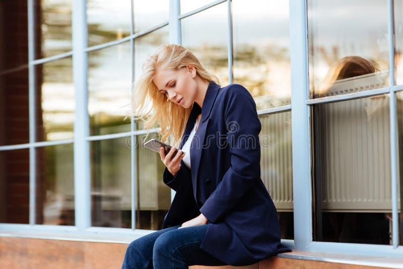 Ungt innehav hennes mobiltelefon på stadsgatan fotografering för bildbyråer