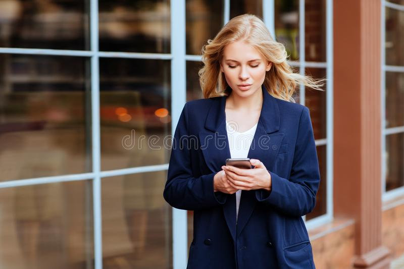 Ungt innehav hennes mobiltelefon på stadsgatan royaltyfri foto