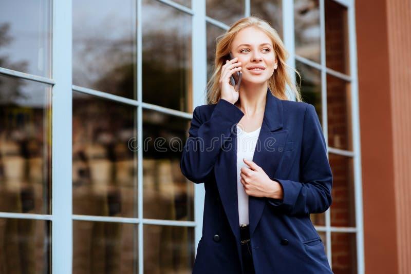 Ungt innehav hennes mobiltelefon på stadsgatan arkivfoton