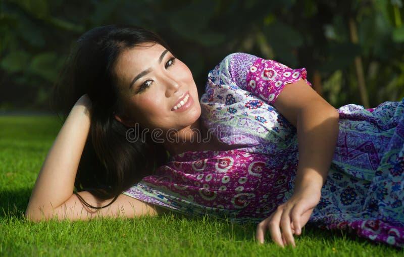 Ungt kopplat av härligt och lyckligt asiatiskt kinesiskt ligga för 20-talkvinna arkivbild