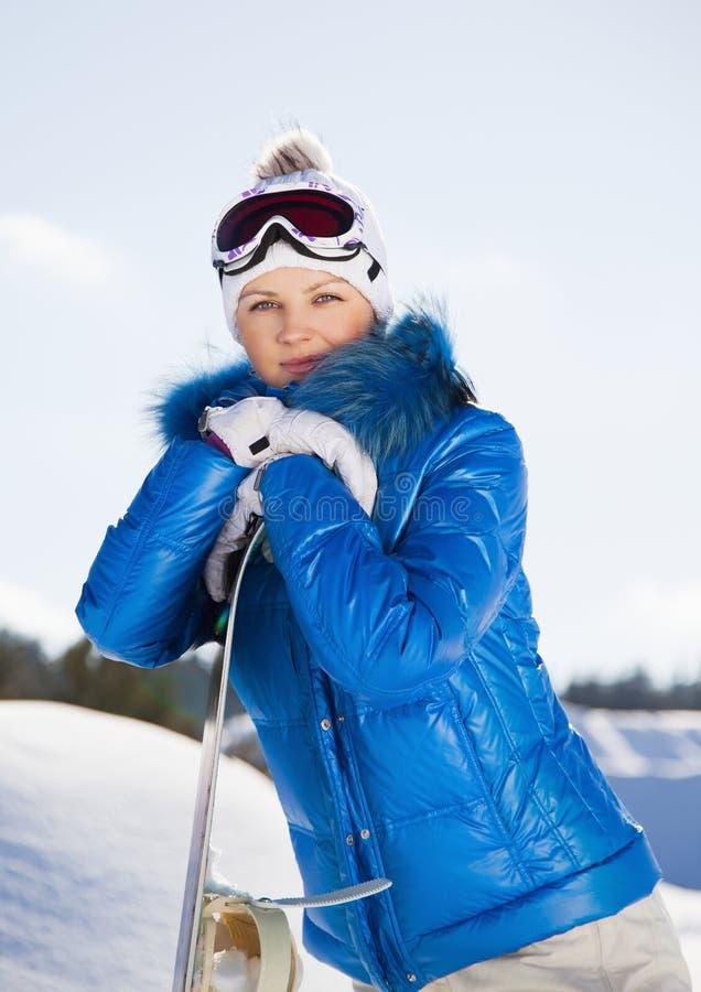 Ungt kvinnaanseende med snowboarden i henne räcker arkivfoton