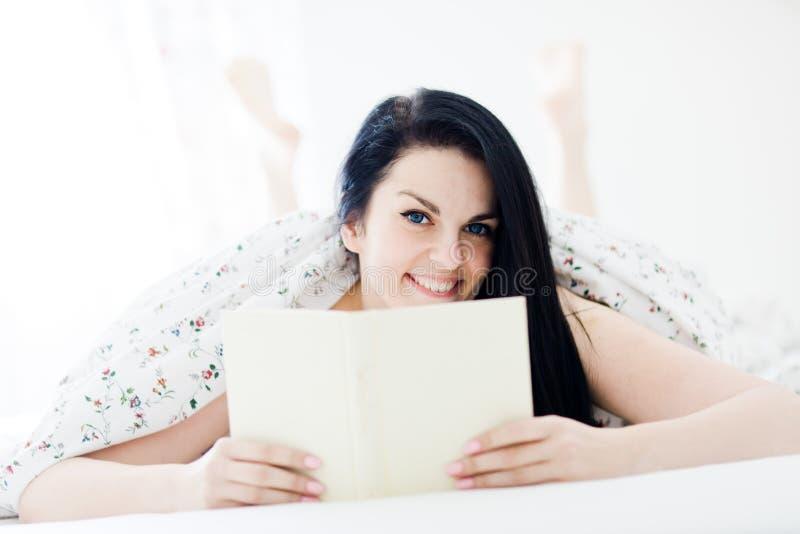 Ungt kvinnakoppla av och läsebok i sovrummet - ben i bakgrund royaltyfria bilder