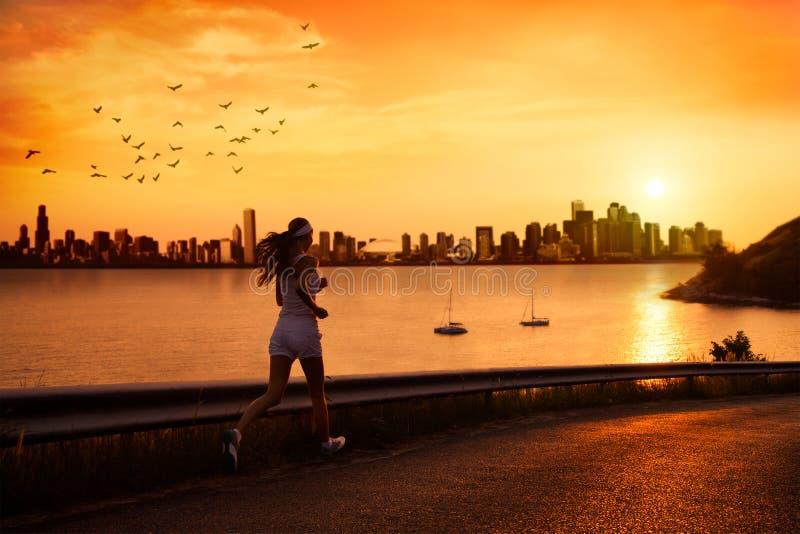 Ungt kvinnaspring på solnedgången royaltyfri foto