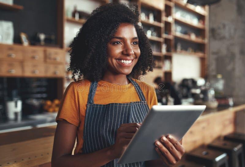 Ungt kvinnligt ägareanseende i kafét som rymmer den digitala minnestavlan royaltyfri fotografi