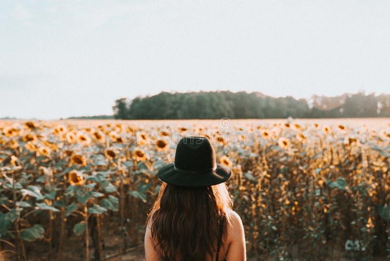 Ungt kvinnligt anseende framme av ett stort härligt solrosfält arkivbild