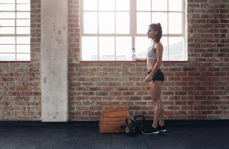 Ungt kvinnligt anseende på idrottshallen royaltyfri fotografi