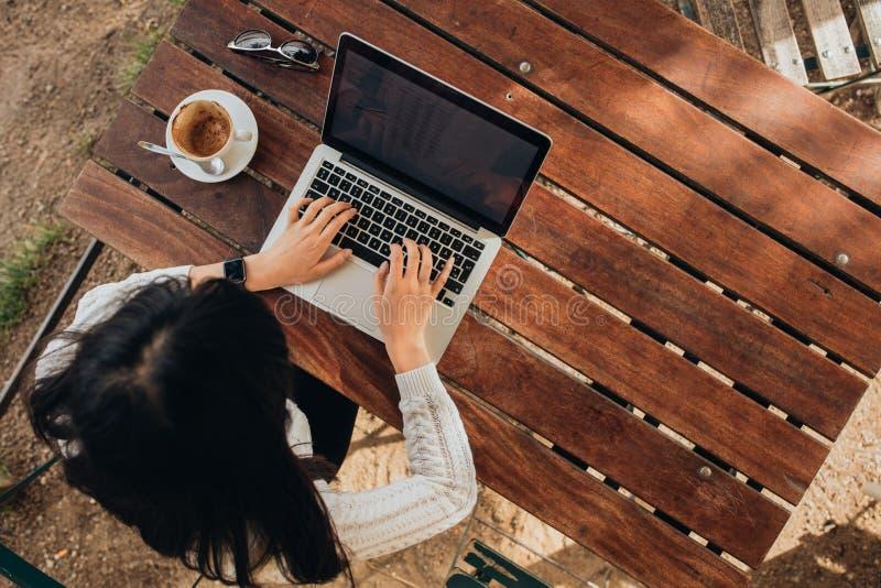 Ungt kvinnligt arbete på hennes bärbar dator på ett kafé royaltyfri fotografi