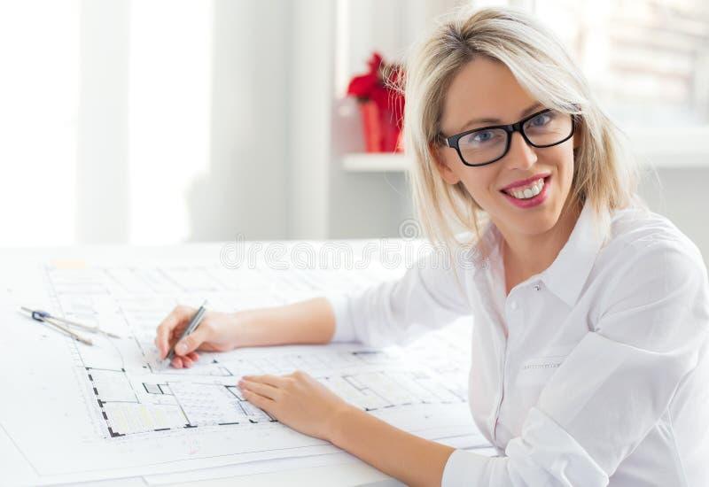 Ungt kvinnligt arkitektsammanträde på hennes skrivbord i kontoret fotografering för bildbyråer