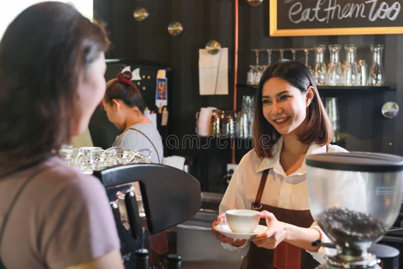 Ungt kvinnligt baristaportionkaffe till kunden i kafé royaltyfri bild