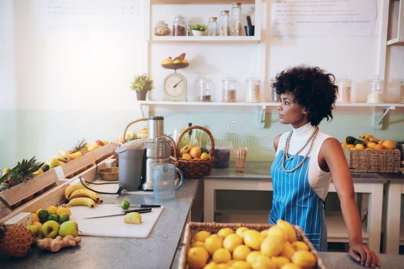 Ungt kvinnligt bartenderanseende på räknaren för fruktsaftstång arkivbild