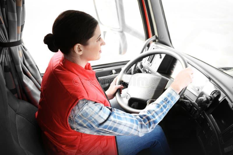 Ungt kvinnligt chaufförsammanträde i kabin av den stora lastbilen royaltyfria foton