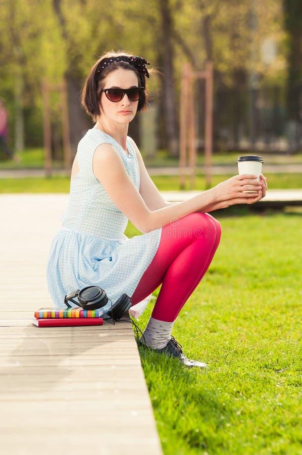 Ungt kvinnligt innehav en kopp kaffe och en avslappnande yttersida royaltyfria foton