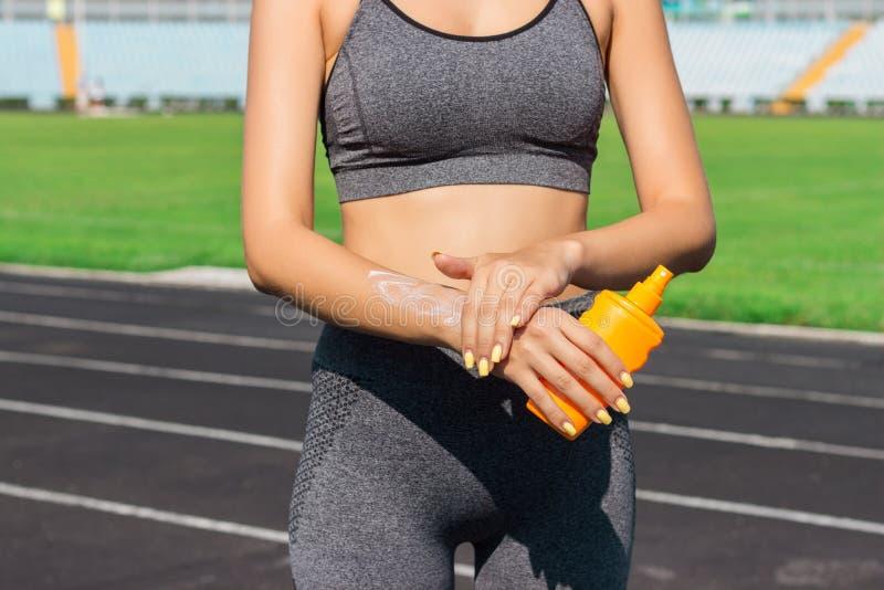 Ungt kvinnligt löpareanseende och sätta sollotion förestående Flicka som använder sunscream för körande övning för sport på somma royaltyfria bilder