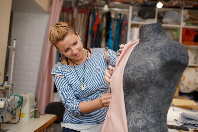 Ungt kvinnligt sömmerskabilagatyg till skyltdockan som använder visare skapa klänningdesign i skräddareseminarium Skräddarebransc royaltyfri bild