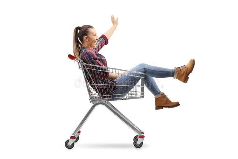 Ungt kvinnligt sammanträde inom en shoppa vagn och vinka arkivfoton