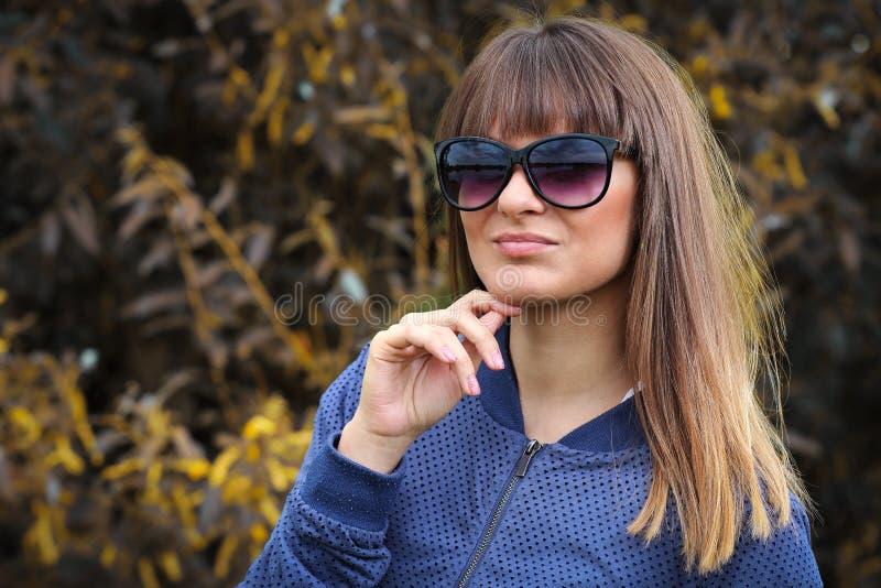 Ungt kvinnligt tonårigt i solglasögon parkerar in Modestående av den attraktiva flickan Härlig trendig kvinna i utomhus- royaltyfria bilder