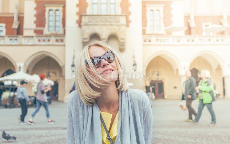 Ungt kvinnligt turist- sammanträde nära torkduken Hall i det gamla centret av Krakow fotografering för bildbyråer