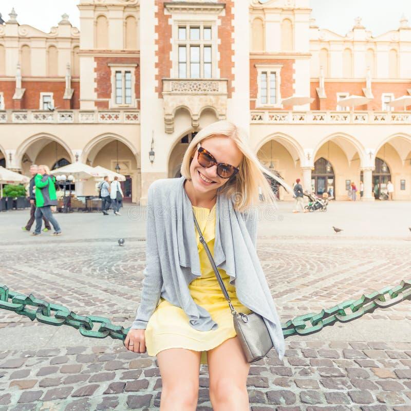 Ungt kvinnligt turist- sammanträde nära torkduken Hall i det gamla centret av Krakow royaltyfria foton