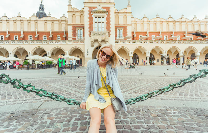 Ungt kvinnligt turist- sammanträde nära torkduken Hall i det gamla centret av Krakow royaltyfri fotografi
