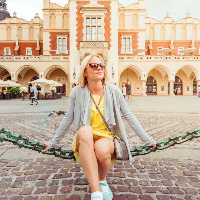 Ungt kvinnligt turist- sammanträde nära torkduken Hall i det gamla centret av Krakow royaltyfri bild