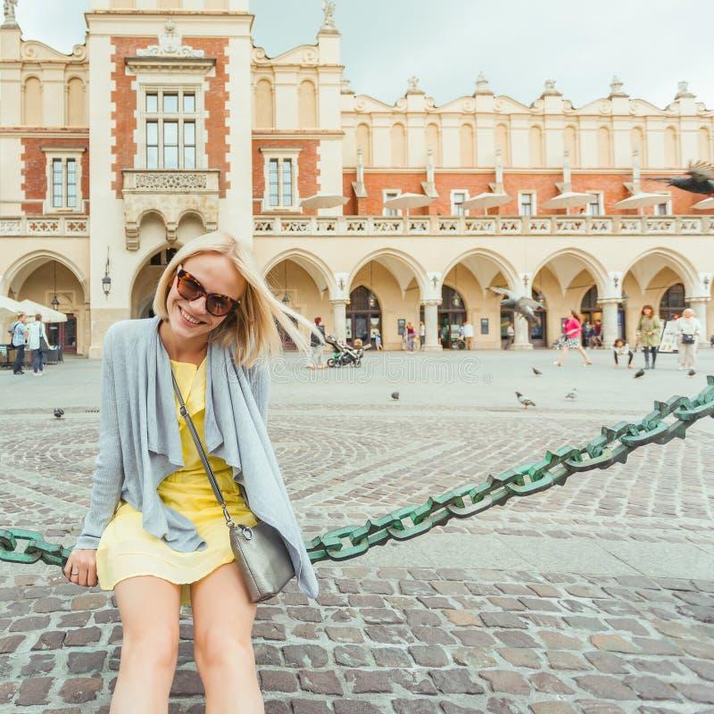 Ungt kvinnligt turist- sammanträde nära torkduken Hall i det gamla centret av Krakow royaltyfria bilder