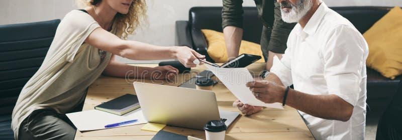 Ungt lag av coworkers som gör stor arbetsdiskussion i modernt kontor Skäggig man som talar med marknadsföringsdirektören och arkivfoton
