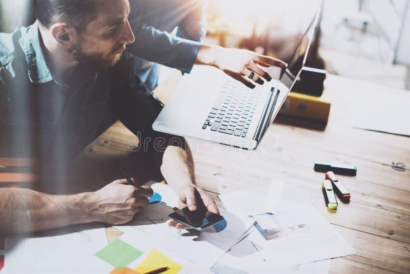Ungt lag av coworkers som gör stor diskussion nytt projekt i modernt kontor Man som använder smartphonen och bärbara datorn Affär arkivfoto