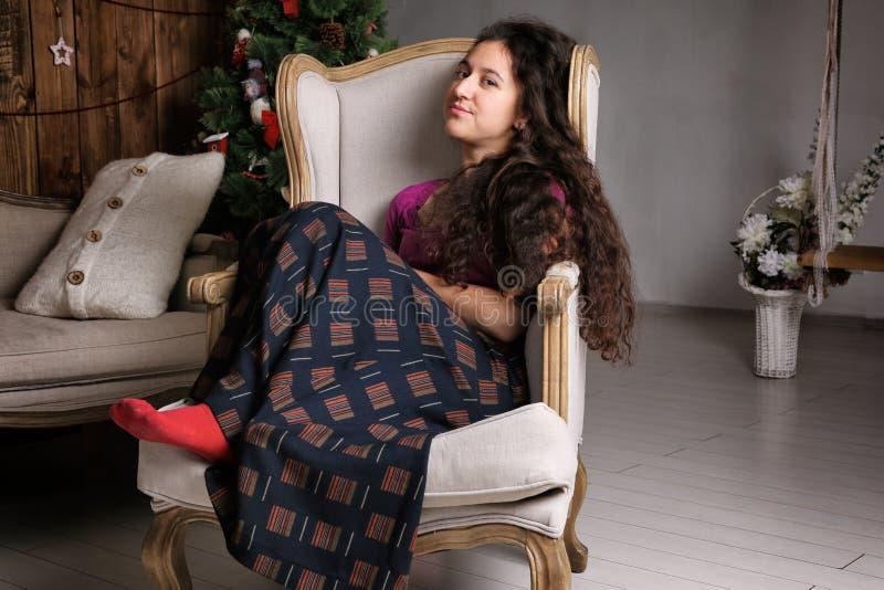 Ungt latinamerikanskt kvinnasammanträde i stol i den lantliga inre och den väntande på berömmen arkivfoton