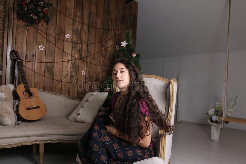 Ungt latinamerikanskt kvinnasammanträde i stol i julinre och den väntande på berömmen arkivfoto