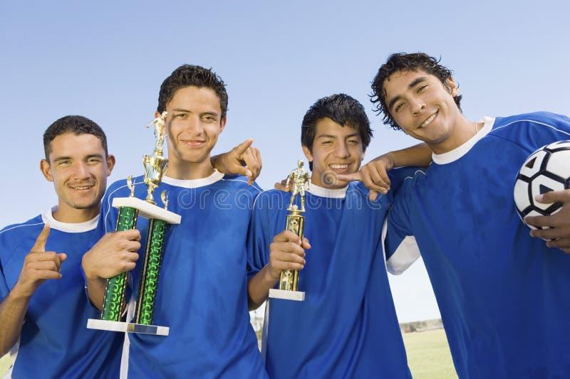 Ungt latinamerikanskt latinskt fotbollslag med trofén royaltyfri bild