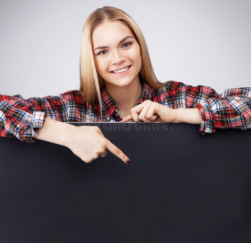 Ungt le för flickahåll för tonåring papper och shower för blond svart tomt på det royaltyfri bild