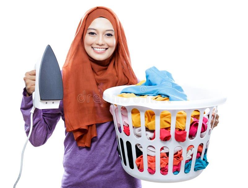 Ungt le för hijabinnehav för kvinna bärande järn och bärande laun arkivfoton