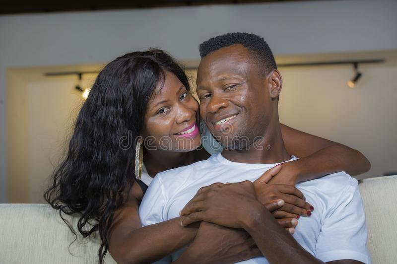 Ungt le för soffa för soffa för vardagsrum för härliga och lyckliga svarta afrikansk amerikanpar som förälskat avkopplat hemmasta royaltyfri bild