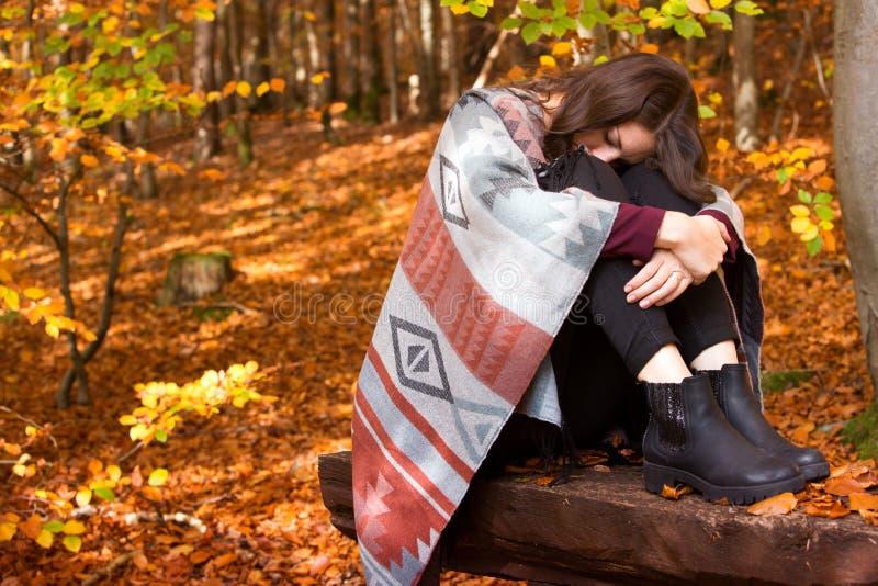 Ungt ledset kvinnasammanträde utanför i höst arkivfoton