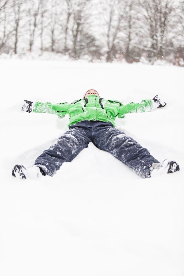 Ungt ligga för pojke som ut sträcks i snön royaltyfria bilder