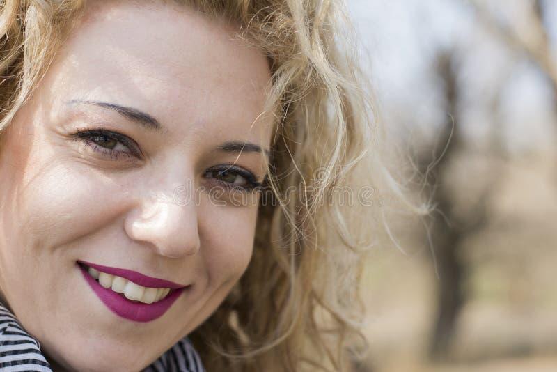 Ungt lockigt blont le för kvinna royaltyfri fotografi