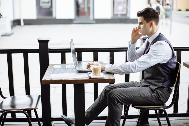 Ungt lyckat sammanträde för affärsman i utomhus- stads- kafé med bärbara datorn och samtal på telefonen royaltyfri foto