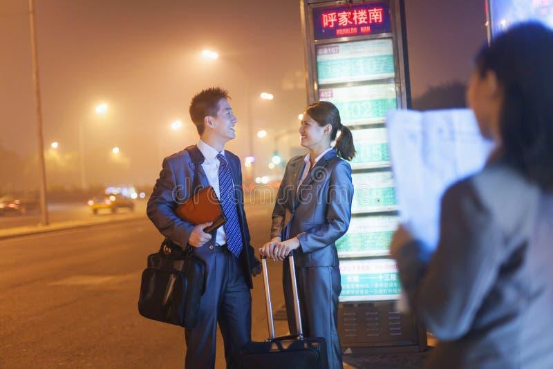 Ungt lyckligt affärsfolk som väntar på en buss på natten arkivfoton
