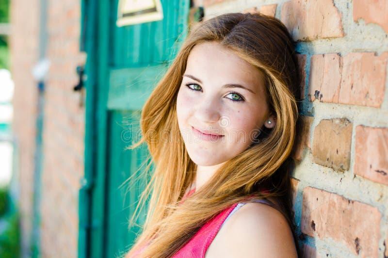 Ungt lyckligt anseende för tonårs- flicka på bakgrund för vägg för röd tegelsten royaltyfri foto