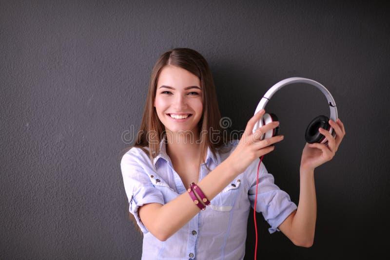Ungt lyckligt flickasammanträde på golv och lyssnande musik royaltyfri bild