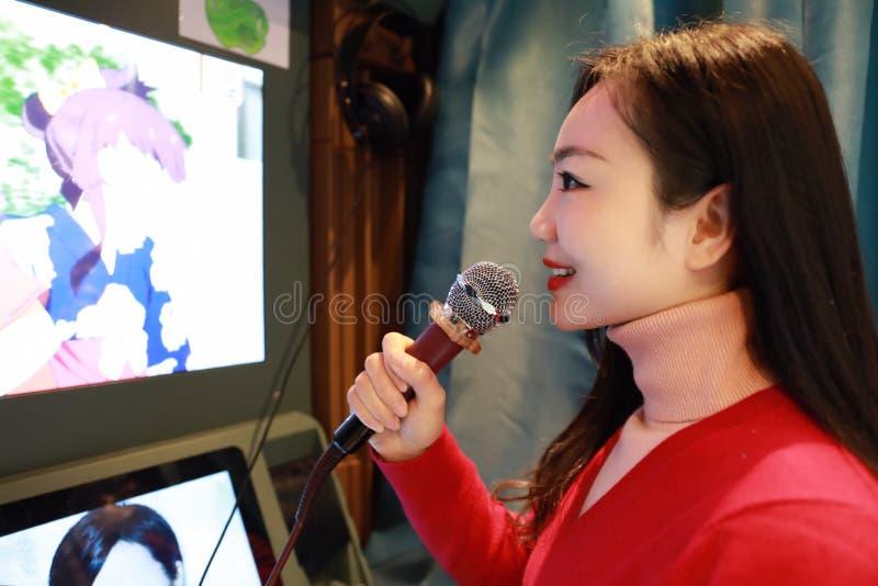 Ungt lyckligt härligt asiatiskt sjunga för kvinna arkivfoton