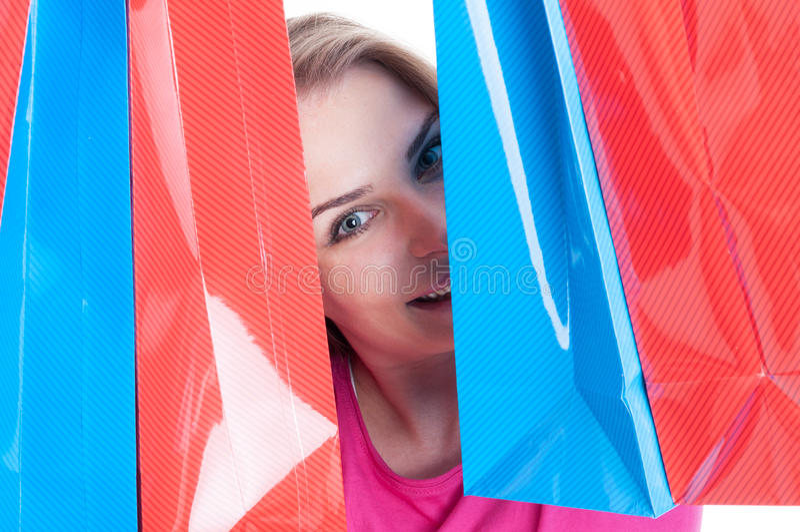 Ungt lyckligt le kvinnanederlag bak kulöra pappers- påsar royaltyfri bild