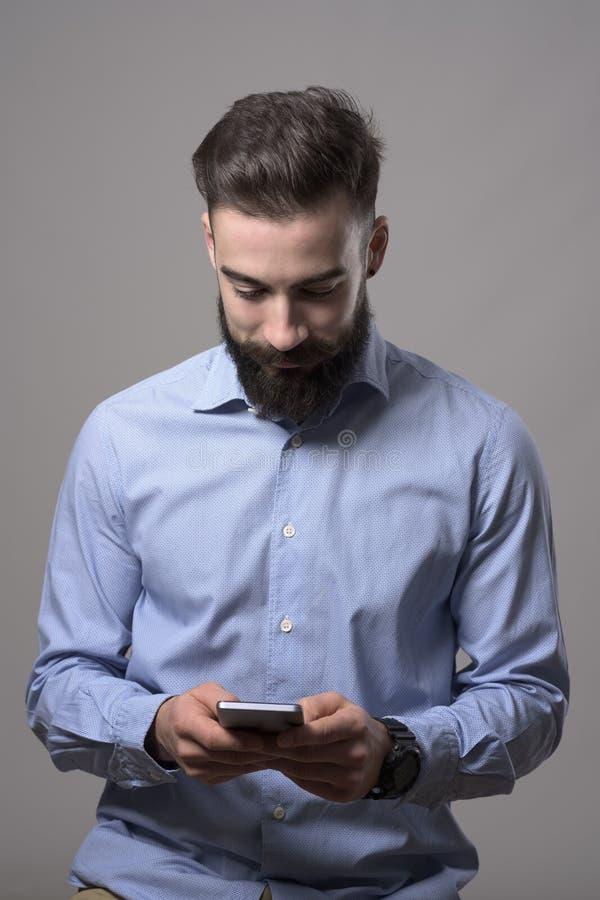Ungt lyckligt le skäggigt stilfullt meddelande för maskinskrivning för affärsman på mobiltelefonen som ner ser på telefonen royaltyfria bilder