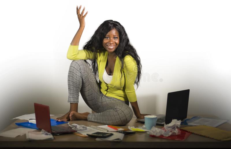 Ungt lyckligt och attraktivt sammanträde för afrikansk amerikanaffärskvinna på det smutsiga skrivbordet för kontor mycket av kopp royaltyfri bild