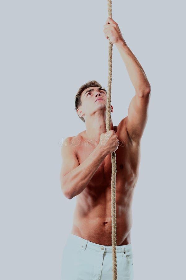 Ungt manligt försöka till att klättra repet och att se upp isolerat på vit bakgrund royaltyfri fotografi