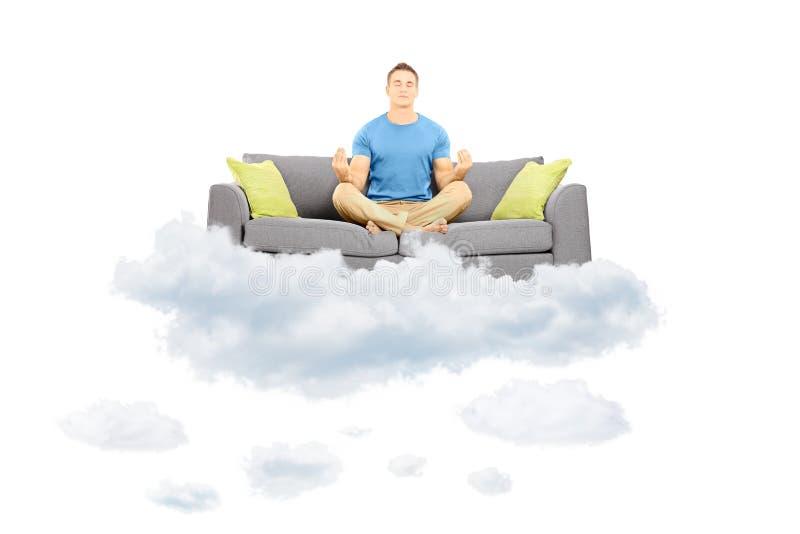 Ungt manligt meditera på en soffa och sväva på ett moln arkivbild