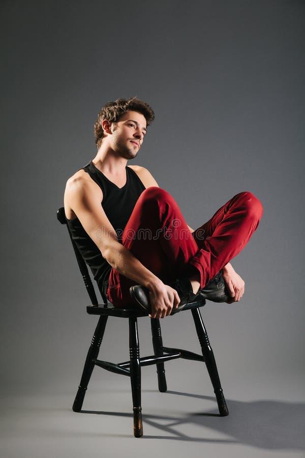 Ungt manligt modellsammanträde på stolen royaltyfria foton