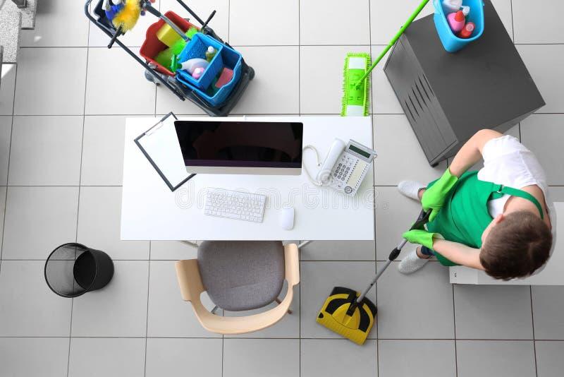 Ungt manligt rengöringsmedel på arbete arkivbilder