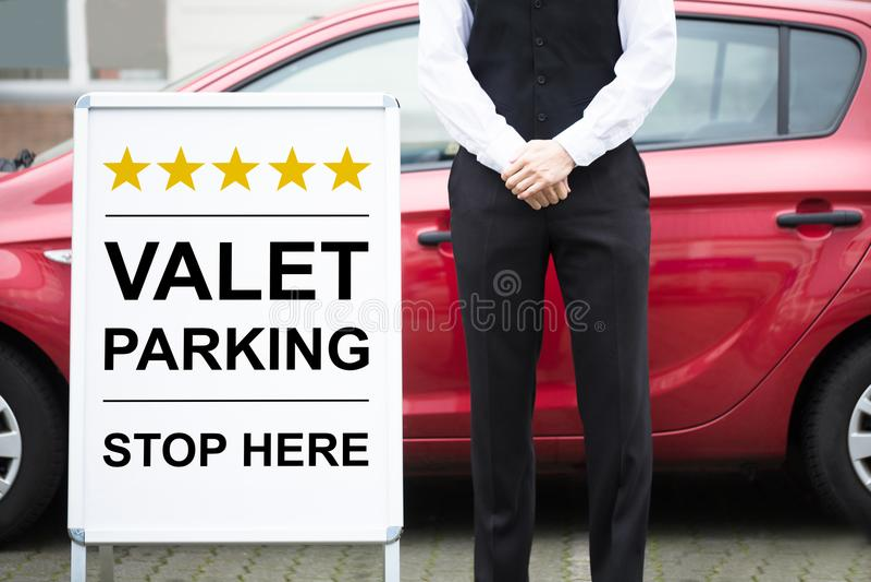 Ungt manligt tecken för betjäntStanding Near Valet parkering royaltyfria foton
